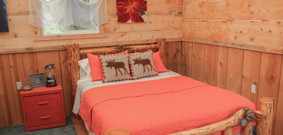 a log bed in a glamping cabin tent