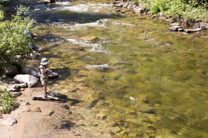 boy catching a trout in idaho wilderness