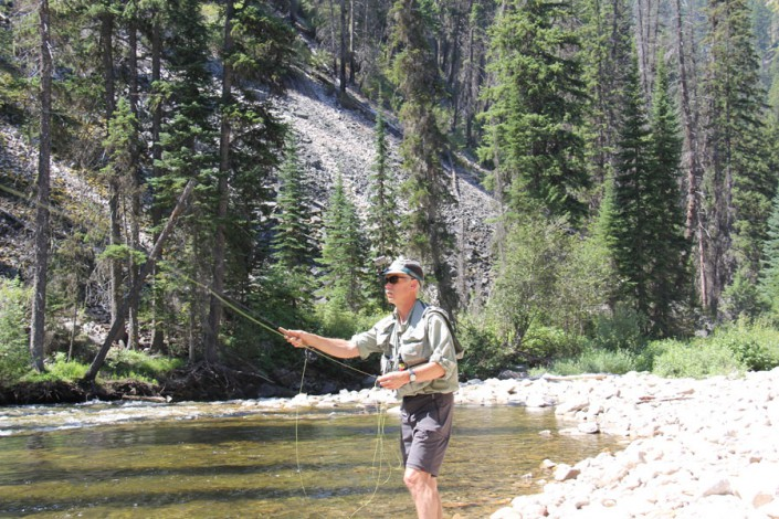 fly fisherman casting into selway river in the idaho wilderness
