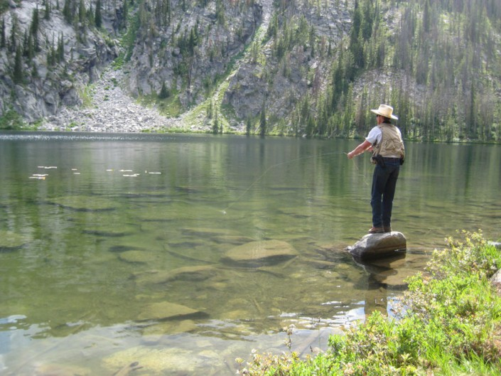 man fishing in a beautiful mountain lake