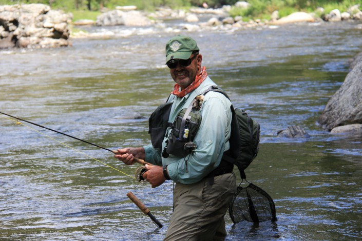 man smiles as he fishes for trout in selway river