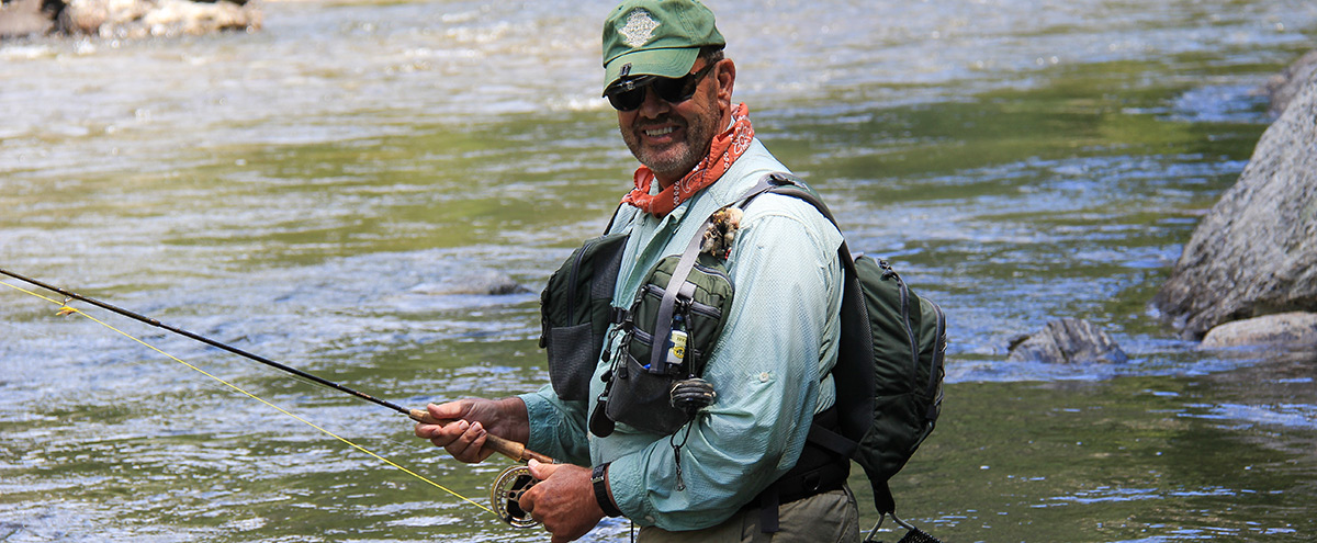 man smiles as he fishes for trout in idaho wilderness